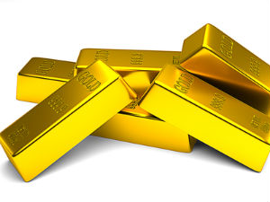 Gold edges lower; strong dollar weighs